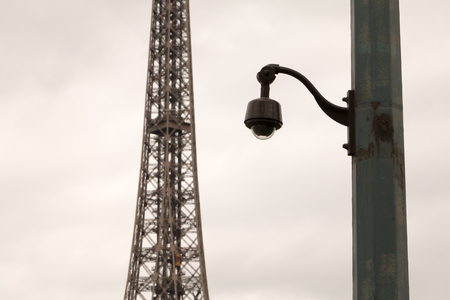 private security: black security camera on a pillar in bad weather in front of the Eiffel Tower