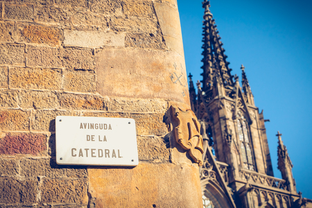marble street sign where it is written in Spanish - Avenue of the cathedral - and in background, cathedral of barcelona, spain Stock Photo