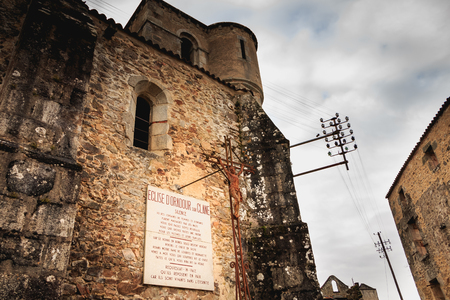 ORADOUR SUR GLANE, FRANCE - December 03, 2017 : on the church destroyed by fire a stone panel where it is written in French - SILENCE here hundreds of women and children were massacred.