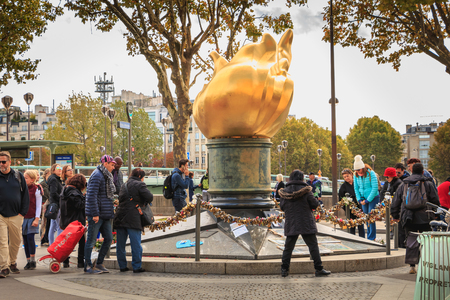 PARIS, FRANCE - October 07, 2017 : tourists gather in front of the flame of freedom, a replica of the flame of the Statue of Liberty of New York. monument made famous by the death of Diana Spencer.