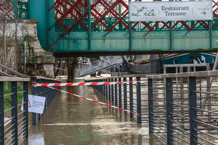 ISSY LES MOULINEAUX near PARIS, FRANCE - January 24, during the flood of winter, a billboard forbids access to the river where it is written - flooded area forbidden access to the public Editorial
