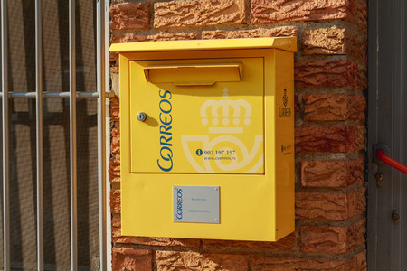 Huesca, Spain - June 21, 2017 : yellow mailbox of the Spanish postal distribution company Correos on a wall in summer