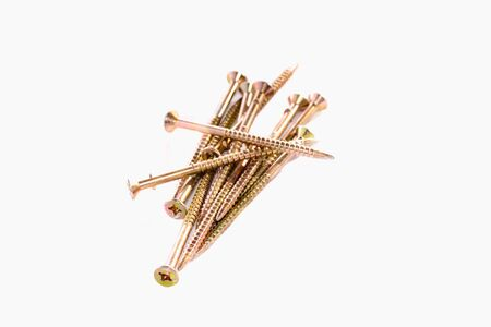 Bunch of yellow zinc coated philips screws on white background Stock Photo