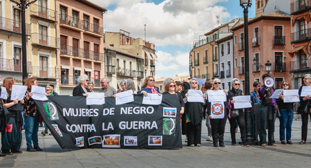 Toledo, Spain - April 28, 2018: in the central square of the city on a spring day, peaceful demonstration of activists Mujeres de Negro (women in black) against the war in Israel