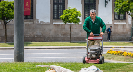 Braga, Portugal - May 23, 2018: Municipal gardeners mowing the grass in the city center on a spring day