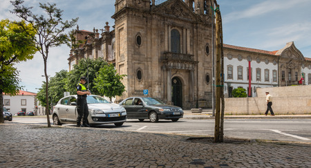 Braga, Portugal - May 23, 2018: policeman checks and writes a traffic ticket on a car in the city center on a spring day 報道画像