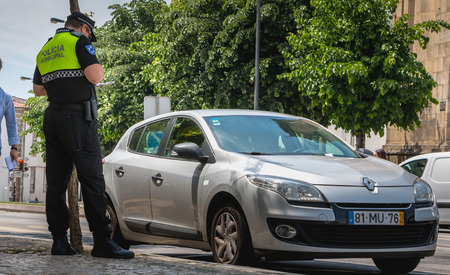 Braga, Portugal - May 23, 2018: policeman checks and writes a traffic ticket on a car in the city center on a spring day Editorial