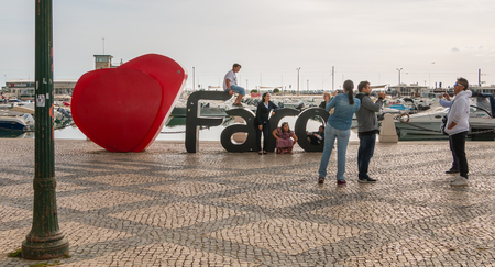 Faro, Portugal - May 1, 2018: Faro city logo name with big letters near the marina in front of which tourists take pictures on a spring day Foto de archivo - 111378457