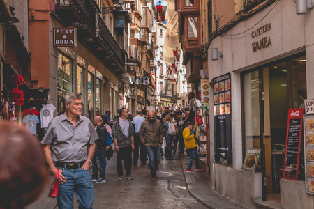 Toledo, Spain - April 28, 2018: Street atmosphere in the traditional shopping district of the city where people walk a spring day
