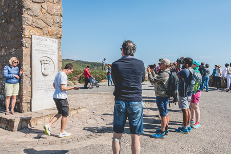 Cabo da Roca near Cascais, Portugal - May 6, 2018: Tourist atmosphere around the cross of Cabo da Roca, the westernmost point of the European continent where tourists walk and take pictures on a spring day Editorial
