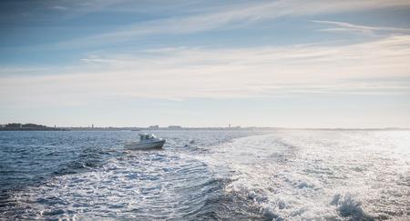 Petit bateau de pêche entrant dans le port accompagné de mouettes Banque d'images
