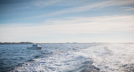 Petit bateau de pêche entrant dans le port accompagné de mouettes