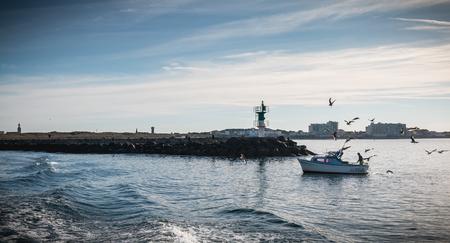 Saint Gilles Croix de Vie, France - 16 septembre 2018 : petit bateau de pêche entrant dans le port accompagné de mouettes un jour d'été