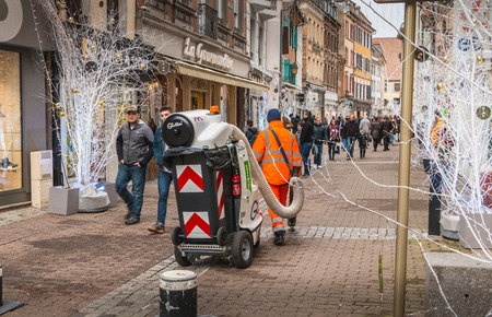 Mulhouse, France - December 23, 2017: City employee clears streets with industrial vacuum during Christmas