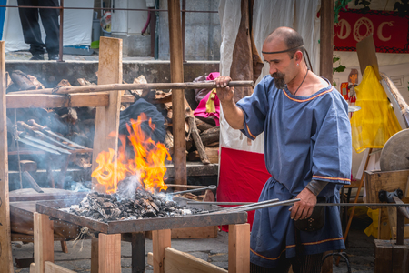 Braga, Portugal - May 23, 2018: Blacksmith who makes metal chafer on a street market giving the passers-by the Roman era that the city knew during the event Braga Romana