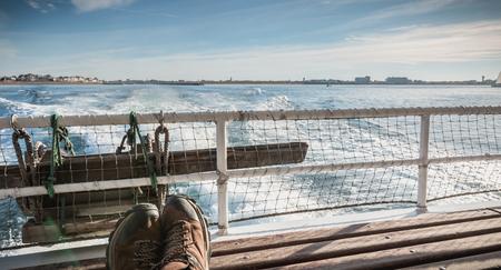 Homme détendu assis à l'arrière d'un ferry quittant le port vers l'île d'Yeu