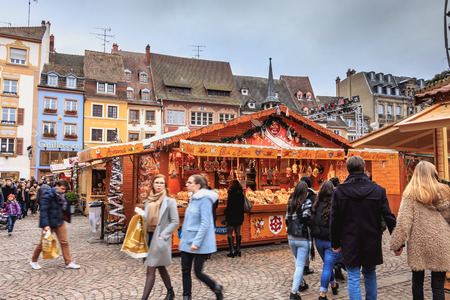 Mulhouse, France - December 23, 2017: Christmas market in front of the cathedral where people are walking on a winter day Stock Photo - 111380094