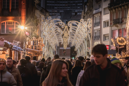 Mulhouse, France - December 23, 2017: Happy people, dressed warmly for the winter walk at night in the Christmas market on a winter day Editorial