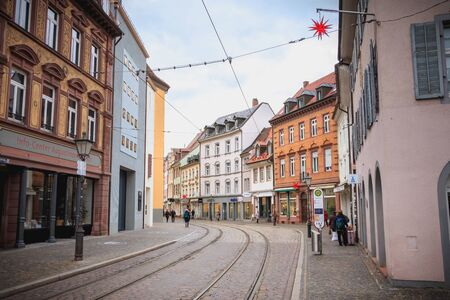 Freiburg im Breisgau, Germany - December 31, 2017: People walking on a small cobblestone street with typical architecture houses in the historic city center on a winter day