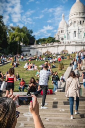 Paris, France - October 6, 2018 - Woman taking a picture of the Basilica of the Sacred Heart among tourists sitting in the grass