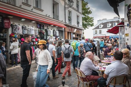 Paris, France - October 6, 2018: street atmosphere on the famous Place du Tertre in Montmartre where artists exhibit their work for curious passers-by who, for some, come to get a portrait