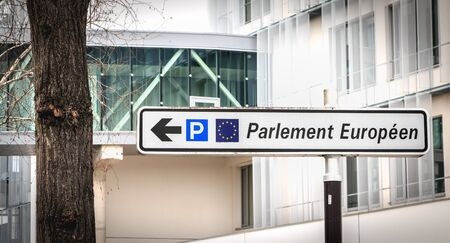 Strasbourg, France - December 28, 2017: in the street, a white road sign indicates the direction of the parking of the European Parliament