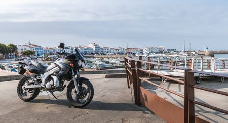 Yeu island, France - September 18, 2018: Motorcycle parked in harbor port Joinville near boats on a summer day Editorial