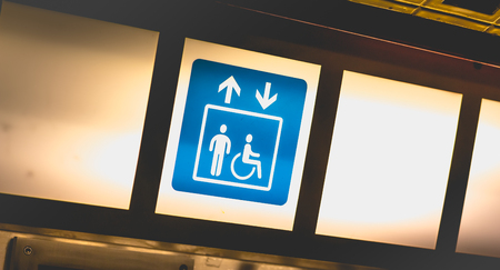 blue sign on bright background indicating access to lifts for persons with reduced mobility Stock Photo
