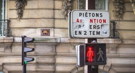 Paris, France - October 7, 2017: on a tricolor traffic light, a sign indicates in French to pedestrians to cross in two stages Editorial