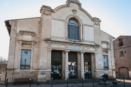 Marseillan, France - December 30, 2018: Man in wheelchair in front of the Henri Maurin theater in the historic city center on a winter day Foto de archivo - 128464603