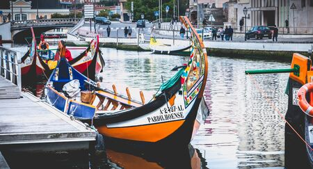 Aveiro, Portugal - May 7, 2018: view at the dock of the famous Moliceiros, traditional boats that used to harvest algae once and now transport tourists to the city canals Foto de archivo - 128464641