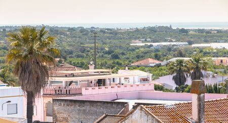 Moncarapacho, Portugal - May 4, 2018: view over the roofs of houses with typical architecture on a spring day Foto de archivo - 128464673