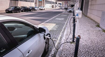 Lisbon, Portugal - May 7, 2018: Electric car in charge in a reserved parking lot of the Nations Park district on a spring day