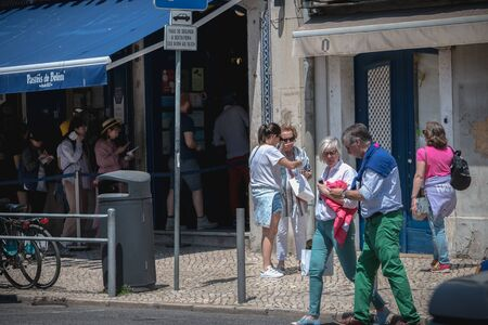 Lisbon, Portugal - May 7, 2018: people coming out of the famous bakery Pasteis de Belem with typical pastries Pastel de Nata a spring day Foto de archivo - 128464683