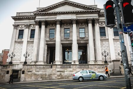 Dublin, Ireland - February 11, 2019: street atmosphere in front of the city hall (Rotunda Hall) with passers-by and cars on a winter day