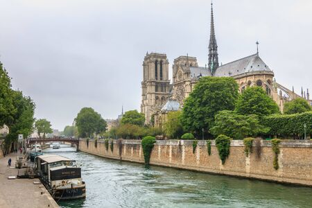 Paris, France - May 8, 2017 - Side view of Notre Dame Cathedral on the Seine with barges on a spring day