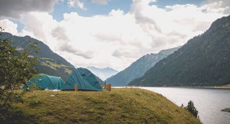 Wild camping atmosphere on a lake in the middle of the Pyrenees in France. with a tent, a gas rechaud
