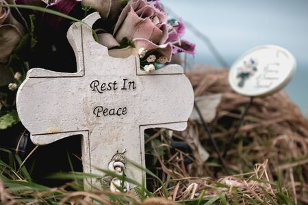 rest in peace written in English on a cross at the edge of a cliff 写真素材