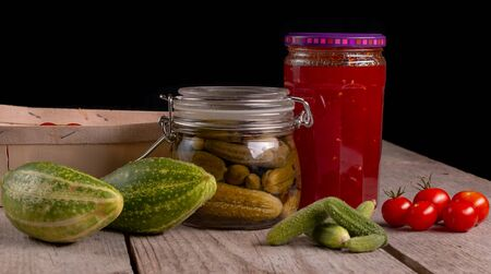 cucumber tomatoes cherry tomato jam canned corinichons on wooden background in studio