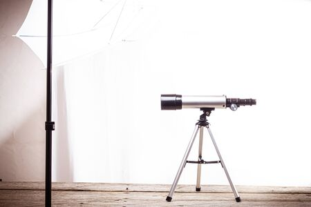 telescope on a white background laid on a rough wooden board Standard-Bild
