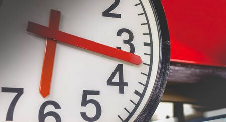 close-up of a white clock with black hand showing 6:17