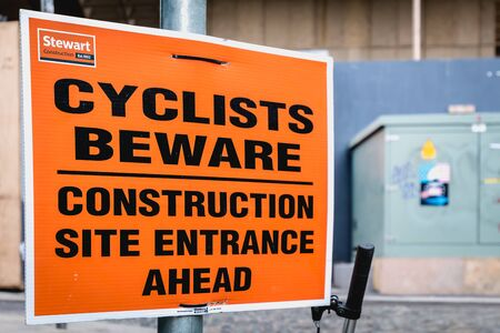 Dublin, Ireland - February 16, 2019: Cyclists Beware - Construction site entrance ahead - on a street sign in the city center on a winter day