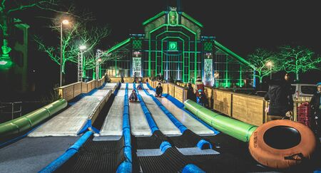 Belfort, France - December 26, 2017: children and adults tobogganing on an ice slide installed at the Christmas party in the city center