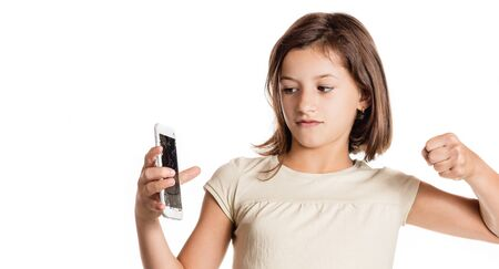 angry little girl holding a smartphone with broken screen in studio