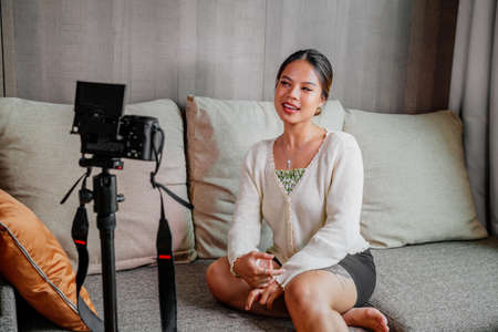 Asian blogger, podcaster or vlogger looking at camera and talking on video shooting with technology. Social media influencer people or content maker concept in relax casual style at home