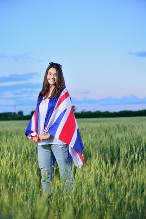 english girl: young smiling girl in a field of wheat. Flag of the Great Britain. The concept of learning English. Stock Photo