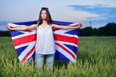 english girl: young girl in a field of wheat. Flag of the Great Britain. The concept of learning English.