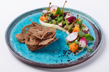 Modern vinaigrette with capers, bread crisps, pumpkin and pear