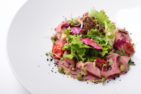 grecian: salad with roast beef, tuna and anchovy sauce. Isolated