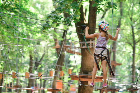 adventure climbing high wire park - girl on course in mountain helmet and safety equipment Stock Photo